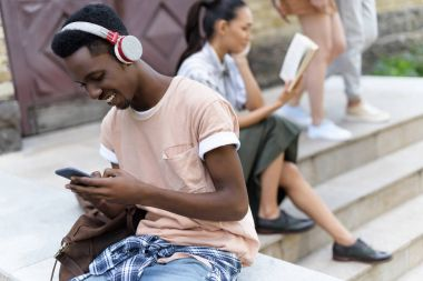 student using smartphone and headphones