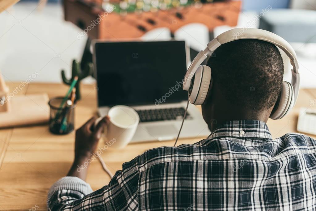 man in headphones using laptop