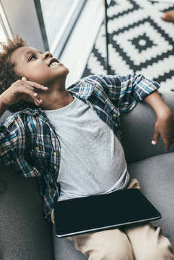 Boy with tablet relaxing on sofa