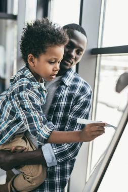 African-american father and son with whiteboard