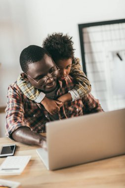 father and son using laptop in office