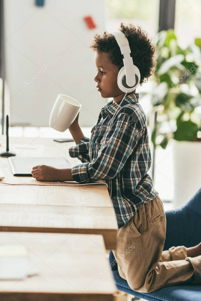 boy with headphones and cup