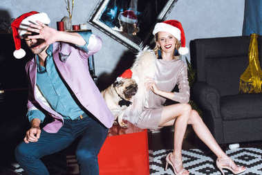 couple with pug in santa hat