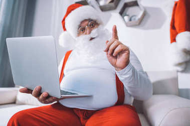 Selective focus of santa claus in hat pointing while holding laptop and sitting on sofa stock vector