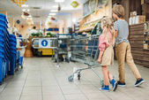 Fotografie kids with shopping cart in supermarket
