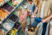 famiglia con il carrello di acquisto in supermercato