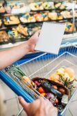 Fotografie man with empty notebook in supermarket