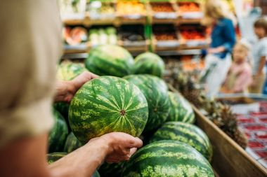 woman picking watermelon in grocery shop
