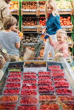 family choosing berries in supermarket