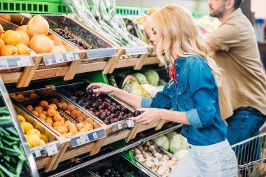 woman choosing plums in grocery shop
