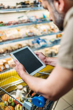 man with tablet in grocery shop