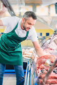 Fotografie prodavače třídění vhodnou syrové maso