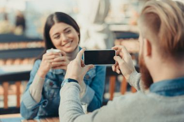 Man taking photo of beautiful girlfriend in cafe outdoors with smartphone stock vector