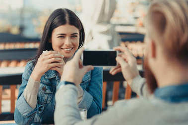 Man taking photo of girlfriend in cafe