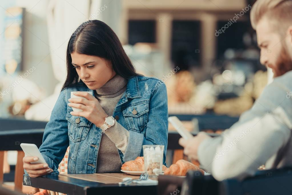 couple looking at smartphones in cafe