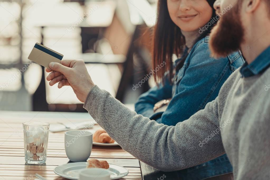 couple paying with credit card in cafe