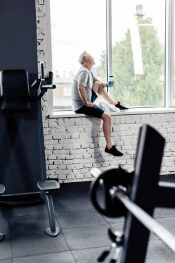 senior sportsman resting in gym