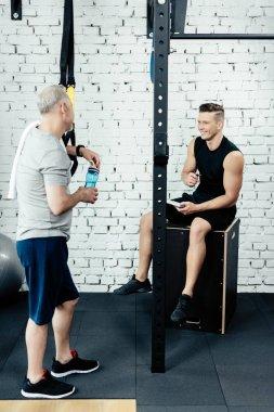 trainer talking with senior sportsman