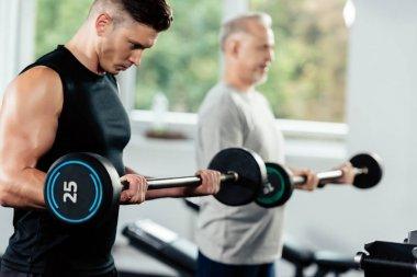 Sportsmen training with barbells