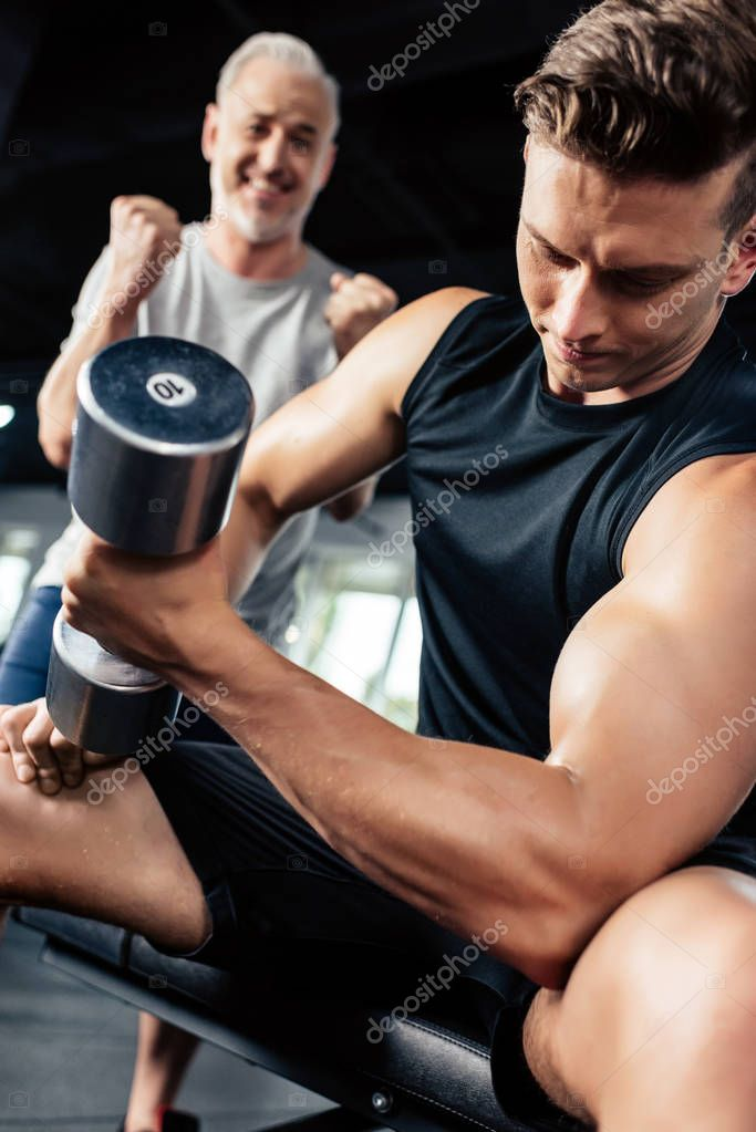 sportsman training with dumbbell