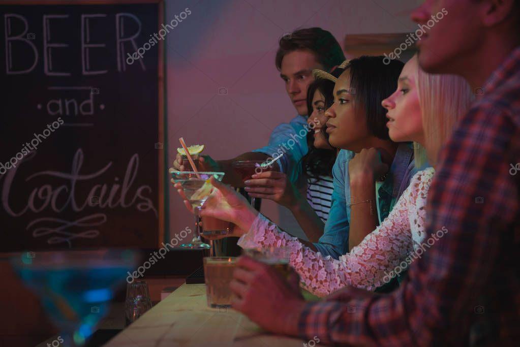 multiethnic friends drinking cocktails in bar
