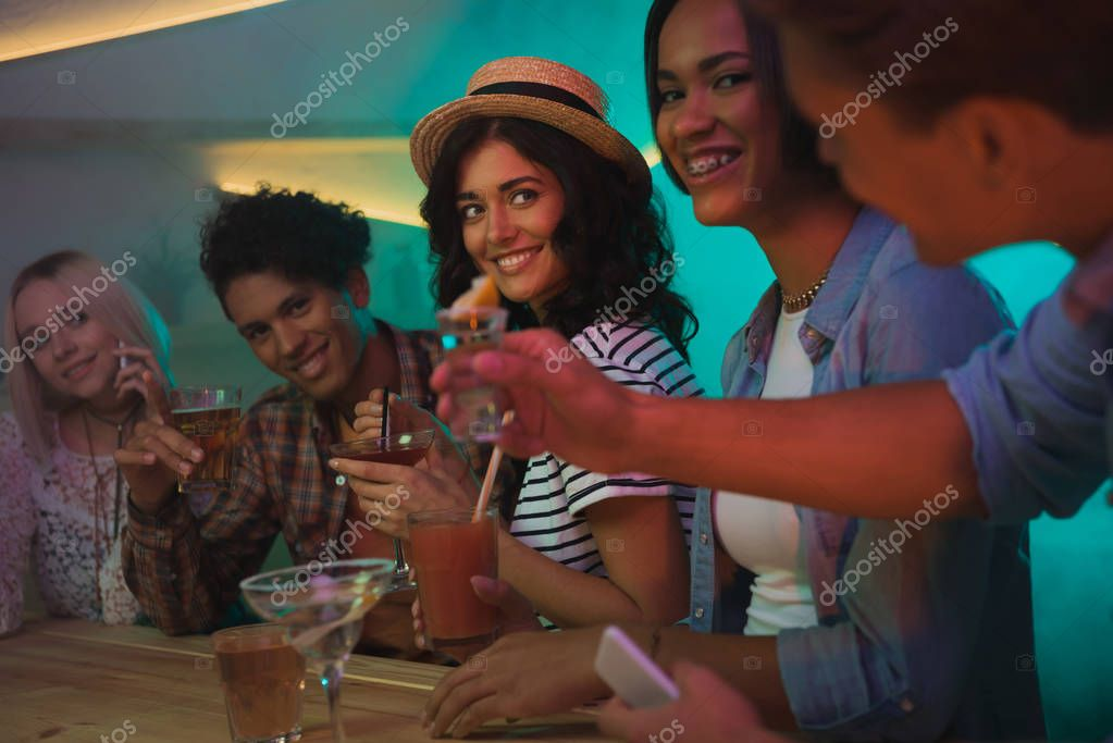 multiethnic friends drinking cocktails in bar