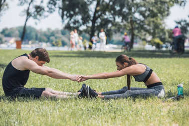 couple stretching in park
