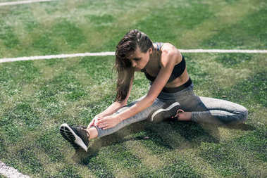 woman stretching on sports field