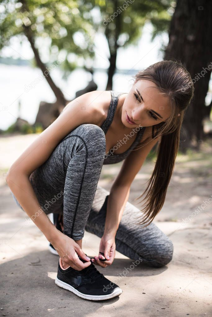 athletic woman tying shoelaces