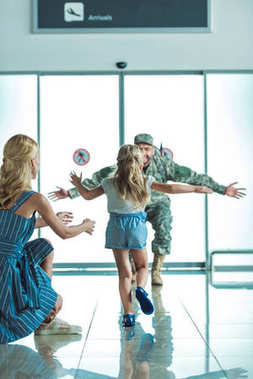 happy child running to father in military uniform