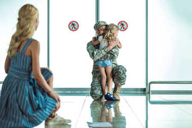 Child hugging father in military uniform