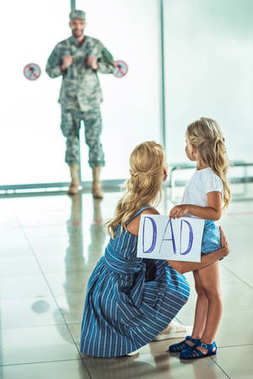 mother and daughter meeting father at airport