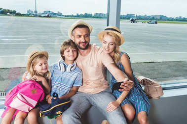 happy family taking selfie in airport