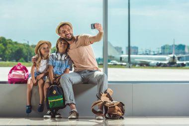 Family taking selfie in airport