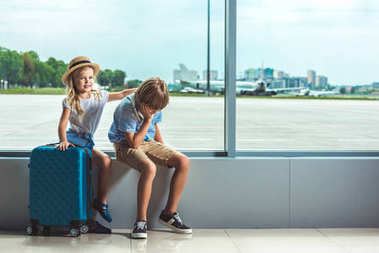 Little siblings sitting on windowsill while waiting in airport stock vector