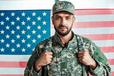Portrait of soldier in military uniform looking at camera against american flag stock vector