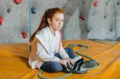 Malá dívka sedící na rohoži v tělocvičně