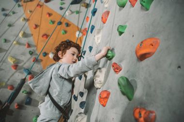 Half-length shot of little boy in a harness climbing a wall with grips at gym stock vector
