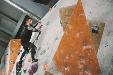 Full-length shot of young man in sportive attire climbing a wall with grips at gym stock vector