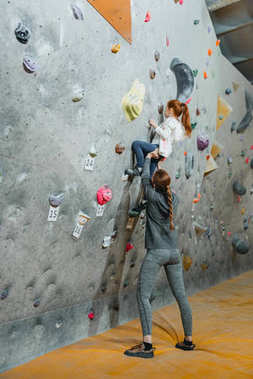 Little girl climbing wall with grips