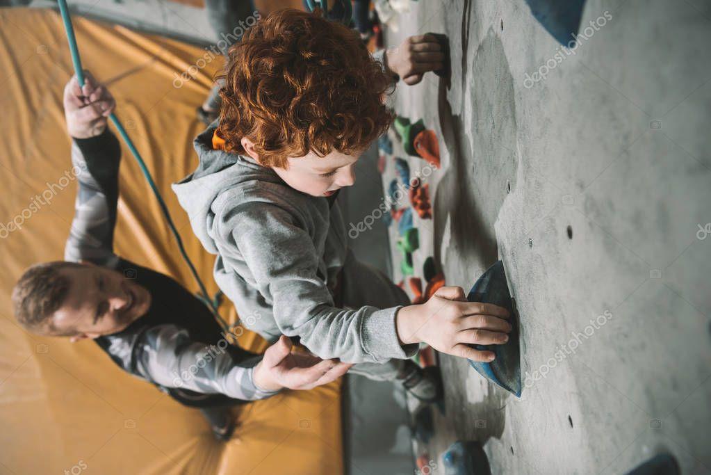 Little boy climbing wall at gym