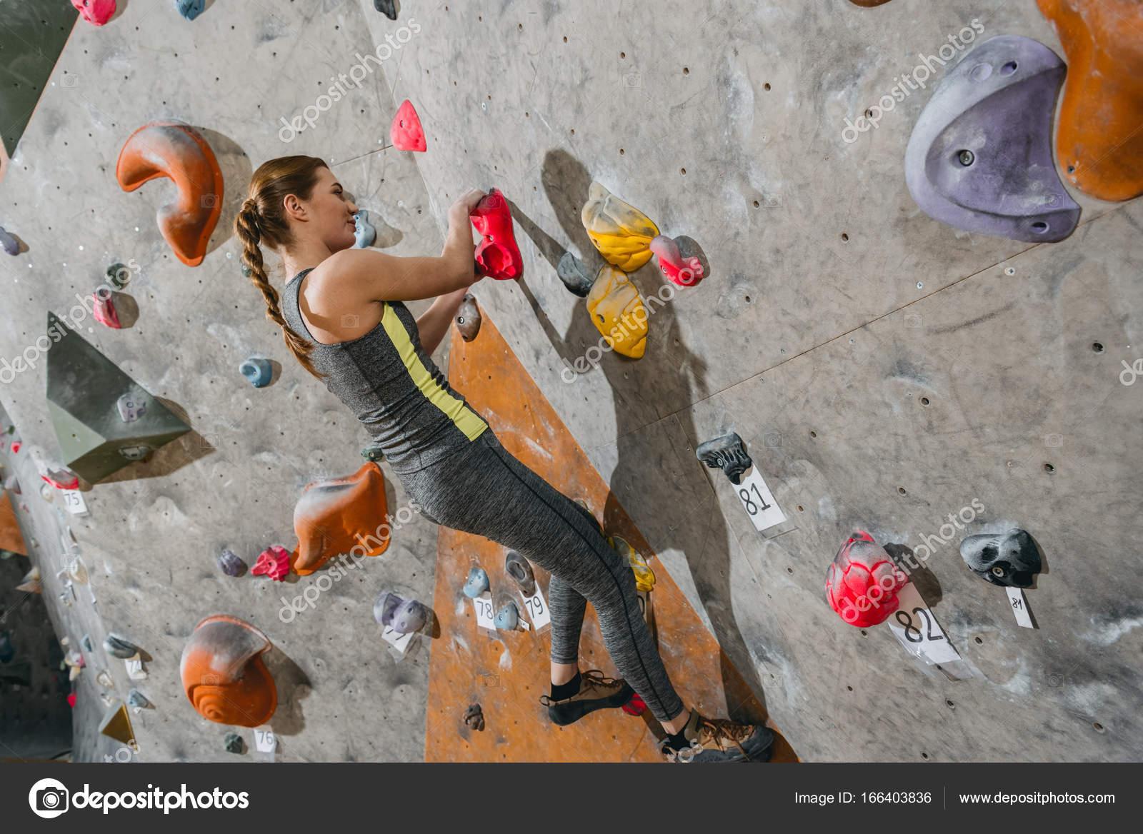 frau kletterwand mit griffen — stockfoto © arturverkhovetskiy #166403836
