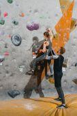 Fotografia giovane donna arrampicata su parete con manopole