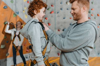 Side view shot of young dad securing little son in a harness for climbing a wall at gym stock vector