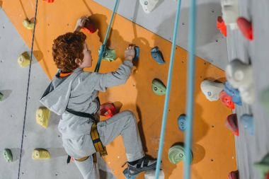 Full-length shot of little boy in a harness climbing a wall with grips at gym stock vector