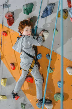 Full-length shot of little boy in a harness climbing a wall with grips at gym and looking at camera stock vector