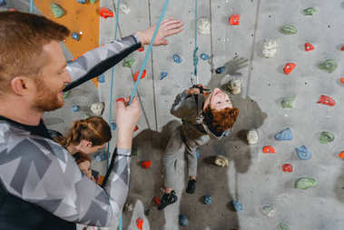 Closeup shot of little boy climbing a wall with grips at gym and his father holding securing rope stock vector