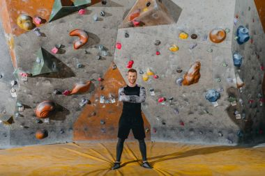 Full-length shot of a young man in sportive attire posing in front of climbing wall stock vector