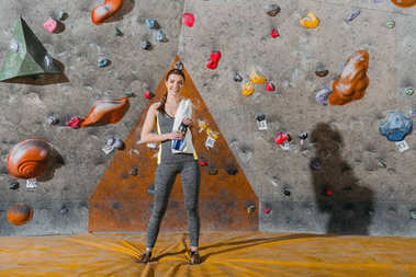 Full-length shot of a young woman in sportive attire posing in front of climbing wall and looking at camera stock vector