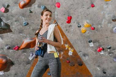 Half-length shot of a young woman in sportive attire posing in front of climbing wall stock vector